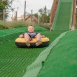 dieťa sa šmýka na tubingovej dráhe